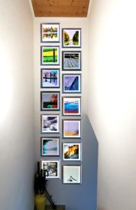 Ansicht einer Bilderhängung mit 14 quadratischen Bildern in einem Treppenhaus